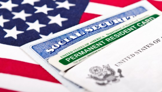 United States of America social security and green card with American flag in the background representing successful Chicago immigrant attorneys fight for client residency