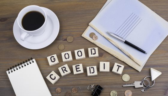 Coffee, pen, money and blocknot on a desk and text Good Credit for top green card attorneys