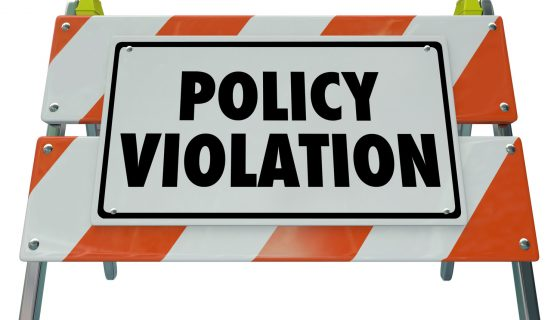 Policy Violation words on a road construction barrier representing the work a chicago employment attorney does.