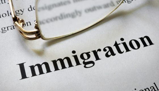 Paper with word immigration and glasses for an immigration lawyer chicago